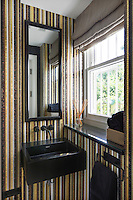 A contemporary bathroom clad with stripes of gold, black and brown mosaic tiles