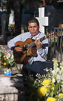 A GUITARIST plays for the dead at the local cemetery during the Day OF THE DEAD - SAN MIGUEL DE ALLENDE, MEXICO..