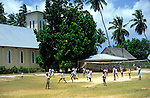 Children playing a volleyball game by the church and school, La Digue island, Seychelles