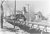 Last narrow gauge freight to leave Santa Fe crossing the trestle over the Santa Fe River.  The Sanctuario de Guadalupe is in the background.<br /> D&amp;RGW  Santa Fe, NM  Taken by McKittrick, Margaret