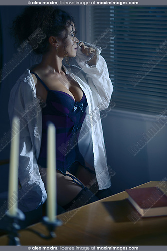 Sensual boudoir portrait of a beautiful sexy woman wearing a men's shirt on top of a corset sitting by the window at night in a dark room lit by street lights