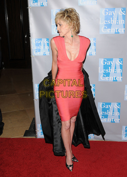 "SHARON STONE .at ""An Evening With Women: Celebrating Art, Music & Equality"" held at The Beverly Hilton Hotel in Beverly Hills, California, USA, April 24th 2009.                                                                     .full length  black trench coat taking off red orange herve leger bandage dress cleavage tight fitting floral print pointy shoes coral .CAP/DVS.©Debbie VanStory/RockinExposures/Capital Pictures"