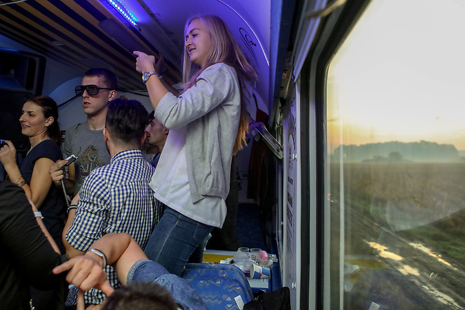 "13.10.2017. - Young Croats are partying hard in a ""Party train"" as the sun rises over plain through which the train is taking them from Croatian capital Zagreb to Serbian Belgrade. This is a train of friendship and joy, where the ""nationality"" of the music played doesn't have any meaning. Photo by Marko Risovic/Kamerades for N-Ost"