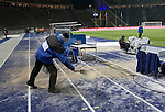 A groundsman spreading grit to prevent player and officials from slipping in the sub-sero temperatures before Hertha Berlin take on Sporting Lisbon in the Olympic Stadium in Berlin in a UEFA Europa League group match. Hertha won the match by 1 goal to nil to press to the knock-out round of the cup. 2009/10 was the the first year in which the Europa League replaced the UEFA Cup in European football competition.