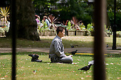 A young man meditates in Russell Square, London.