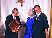 United States President George H.W. Bush and first lady Barbara Bush present the National Medal of Arts to Polish poet, prose writer, translator and diplomat Czesław Miłosz during a ceremony in the East Room of the White House in Washington, DC on November 19, 1989. <br /> Credit: Ron Sachs / CNP