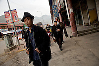 People walk along the streets of Xiahe, Gansu, China.  Xiahe, home of the Labrang Monastery, is an important site for Tibetan Buddhists.  The population of the town is divided between ethnic Tibetans, Muslims, and Han Chinese.