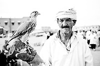 Black and white portrait photo of a man with a bird of prey in Djemaa El Fna Square, Marrakech (Marrakesh), Morocco, North Africa. This black and white portrait photo of a Berber man with a bird of prey shows one of the numerous forms of entertainment, games and performances in Djemaa El Fna Square.