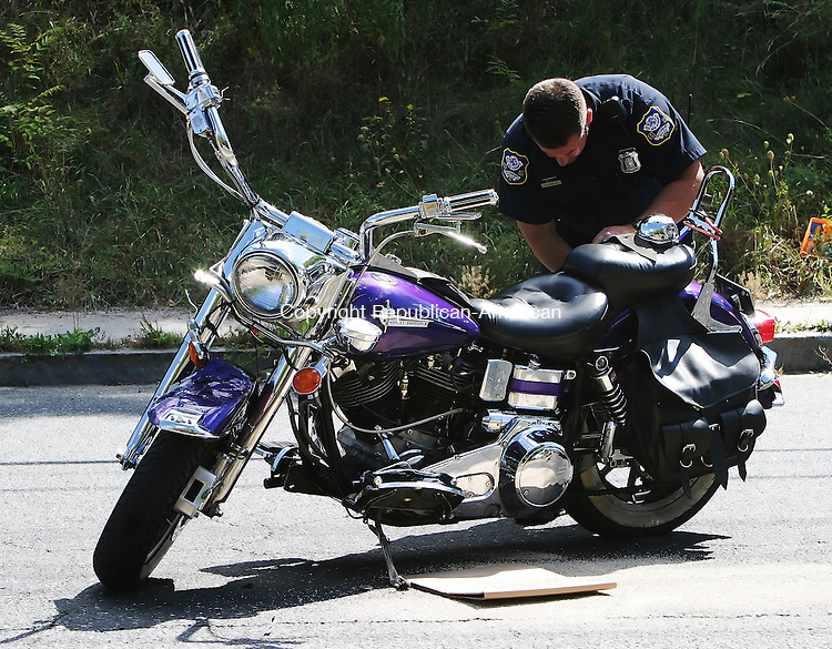 WATERBURY, CT- 10 SEPTEMBER 2005-091005BZ04-  Waterbury Police Officer Brent McLay looks for information at the scene of a motorcycle accident near the intersection of Sylvan Avenue and Washington Street in Waterbury Saturday.  <br /> Jamison C. Bazinet / Republican-American