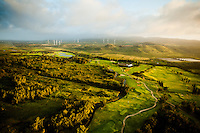 An aerial view of the golf course next to Turtle Bay Resort at sunset, with windmills in the distance, O'ahu.