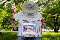 NEW YORK, NY - MAY 27: Artist Jorge Rodríguez organizes the doctor's photo to continue painting the eyes on May 27, 2020 in Queens, New York. The artist Jorge Rodríguez Gerada makes a stunning mural in Flushing Meadows, Corona Park to Dr. Ydelfonso Decoo, an immigrant doctor who died of complications from Coronavirus. The mural is also made in gratitude to the millions of medical workers who have given their lives to fight COVID-19. (Photo by Pablo Monsalve / VIEWpress via Getty Images)
