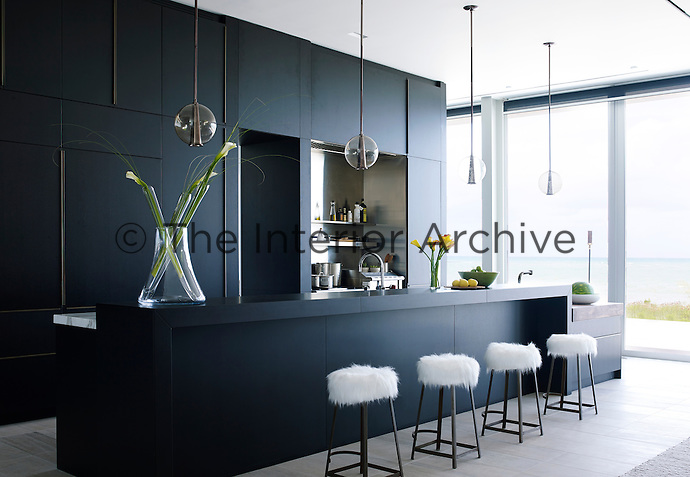An Italian kitchen can carry off its dramatic black shade with bronze detailing in this large double-aspect space, softened further by strokeable stools. It's a high-functioning cook's kitchen, but all preparation areas are hidden behind the bar with a walk in pantry and butlers kitchen behind the kitchen wall.