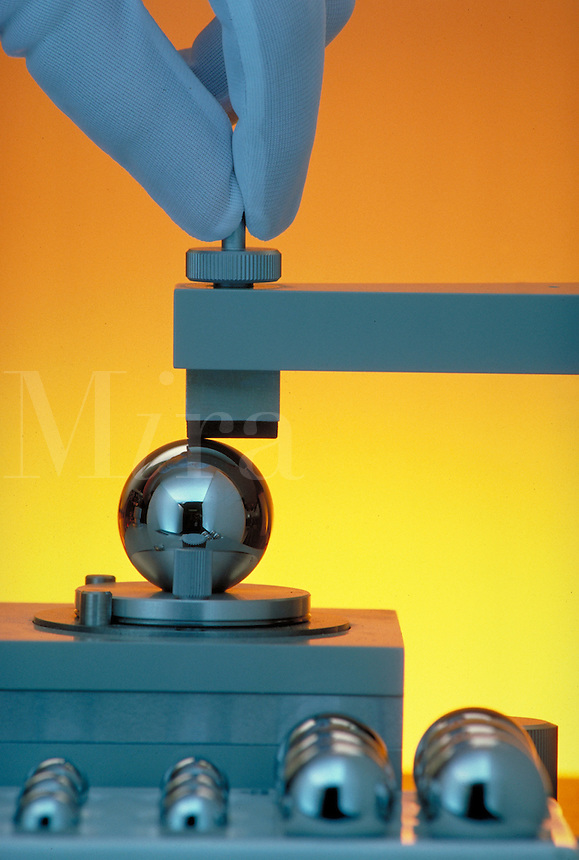 Ball Bearing Testing; measurement, equipment, gloved fingers applying machinery, yellow orange background.