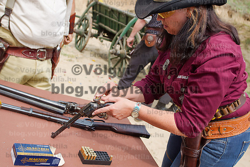 Competitor loads her weapon during the Cowboy Action Shooting European Championship in Dabas, Hungary on August 11, 2012. ATTILA VOLGYI