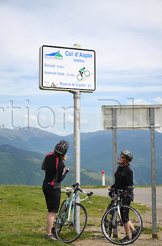 05.06.2012. Pyrenees Mountains, France.  Two cyclists looking at a sign on Col d'Aspin mountain pass (1489m) in the French Pyrenees, which indicates the climb of the pass. Col d'Aspin, with a steeper climb from the east, was already part of the Tour de France for more than 60 times.