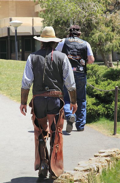 Male Caucasian cowboy following a male motorcycle gang member, along the South Rim of Grand Canyon National Park, Grand Canyon Village, Arizona. . John offers private photo tours in Grand Canyon National Park and throughout Arizona, Utah and Colorado. Year-round.