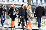 Tourist walk with boots and plastic bags to protect their shoes on flooded St Mark's square during an acqua alta (high-water). The Acqua Alta, a convergence of high tides and a strong sirocco, reached 125 centimetres in Venice, on November 20, 2013.  <br /> &copy; Pierre Teyssot