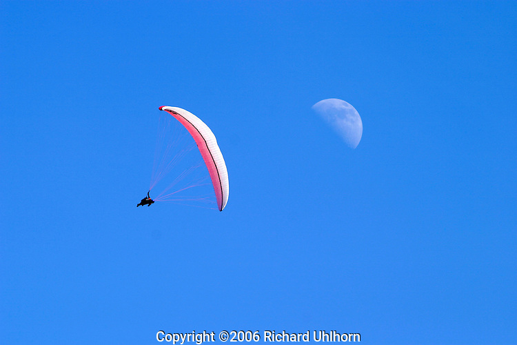 A paraglider competing in the 2006 National Paragliding Championships in Chelan, Washington, USA, spirals downward towards a landing zone.