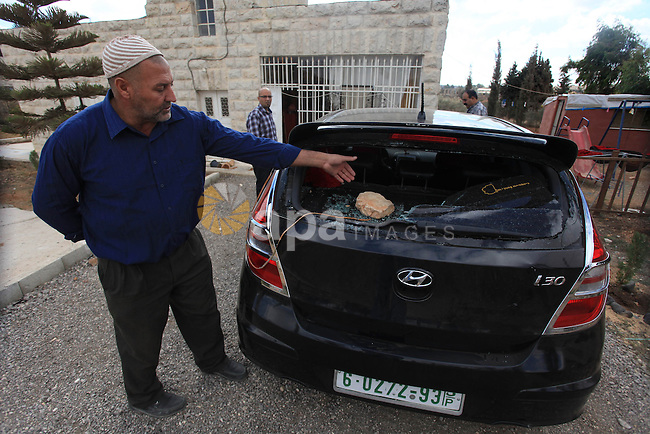 A Palestinian man from Mesleh family inspects his crashed car following the attacks of Israeli settlers in Jalazoun refugee camp near the West Bank City of Ramallah on Oct. 6, 2013. Prime Minister Benjamin Netanyahu said Sunday he holds the Palestinian Authority responsible for a suspected Palestinian militant attack on a young Israeli girl. Relatives of the 9-year-old girl said she was shot by a Palestinian gunman in the West Bank settlement of Psagot Saturday night. There was no claim of responsibility on the attack, but militants in the Gaza Strip praised the attack. Photo by Issam Rimawi