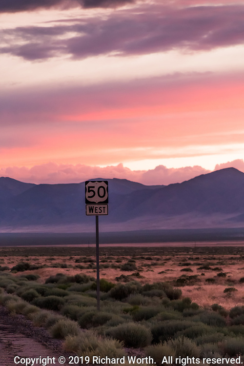 "The highway sign identifying U.S. Route 50, at sunset, along a deserted stretch of what is called, ""The Lonliest Road in America"" in the desert between Austin and Fallon, Nevada."
