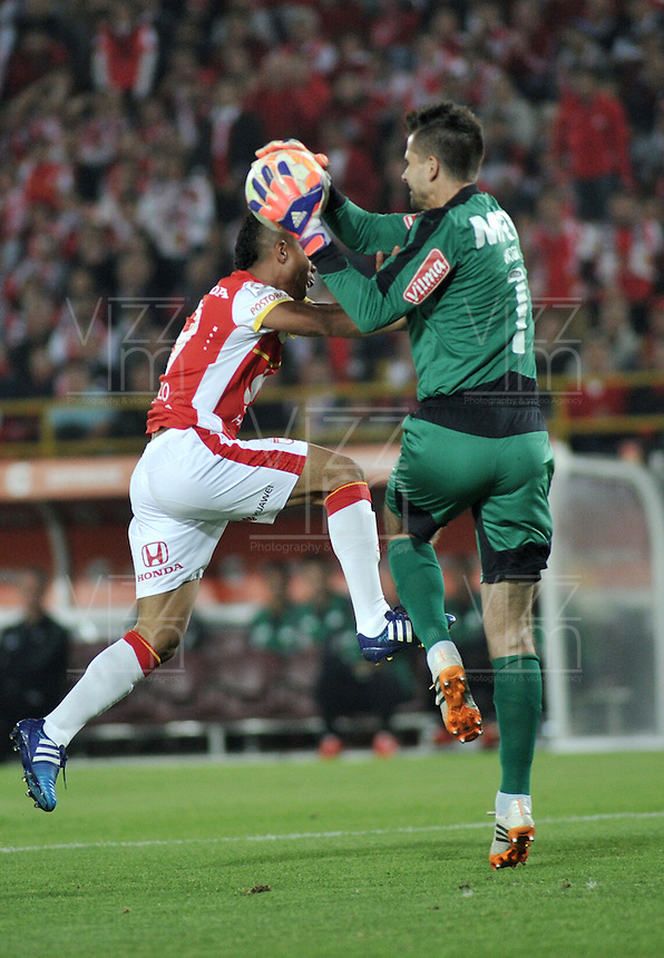 BOGOTA- COLOMBIA – 18-03-2015: Wilson Morelo (Izq.) jugador del Independiente Santa Fe de Colombia, disputa el balon con Victor (Der.) portero de Atletico Mineiro de Brasil, durante partido entre Independiente Santa Fe de Colombia y Atletico Mineiro de Brasil, por la segunda fase, grupo 1, de la Copa Bridgestone Libertadores en el estadio Nemesio Camacho El Campin, de la ciudad de Bogota. / Wilson Morelo (L) player of Independiente Santa Fe of Colombia, figths for the ball with Victor (R) goalkeeper of Atletico Mineiro of Brasil during a match between Independiente Santa Fe of Colombia and Atletico Mineiro of Brasil for the second phase, group 1, of the Copa Bridgestone Libertadores in the Nemesio Camacho El Campin in Bogota city. Photo: VizzorImage / Luis Ramirez / Staff.