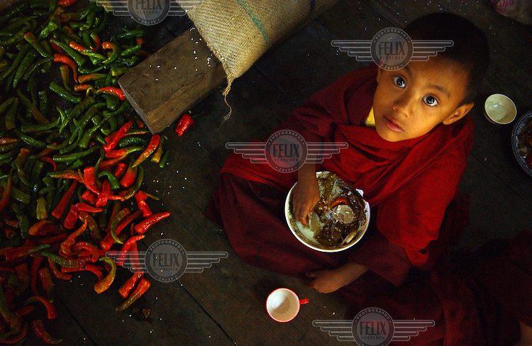 A young monk eats breakfast beside a pile of chillis on the Old Dzong (monastery) of Trashi Yengtse village.