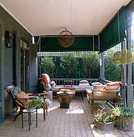 Large green roller blinds provide privacy and protection from the sun on this sheltered terrace which is furnished with a pair of chaise-longue and a Goan deck chair
