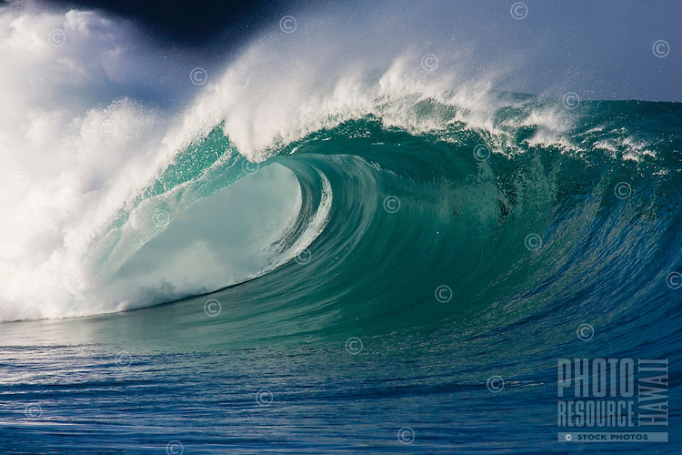 Large beautiful wave with dark cliff in the background.  Waimea Bay shore break on the North Shore of Oahu, Hawaii.