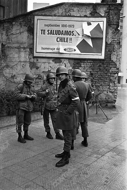 Checkpoint in the aftermath of the coup, soldiers in front of a billboard celebrating the aniversary of the Chilean constitution. Santiago, Chile, September 1973