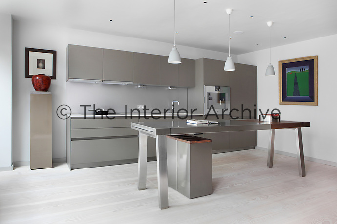 The ultra modern kitchen next to the dining area is furnished with grey units lit by recessed ceiling lights, while a stainless steel work bench with an integrated wooden chopping block is lit by pendant lights in a pale grey