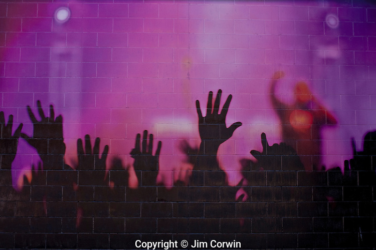 Concert mural on wall with fans waving hands above head