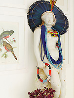 A classical statue in the entrance hall has been decked out in an African headdress and ropes of beads