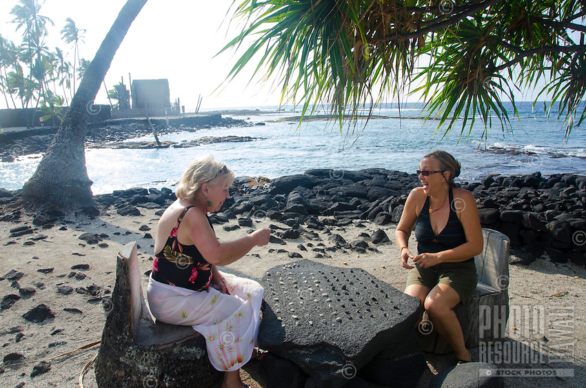 Two women tourists playing konane, or Hawaiian checkers, at Pu'uhonua o Honaunau (or City of Refuge), South of Kona, Big Island of Hawaii