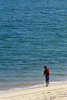 Female in red shirt surf fishing Nantuck