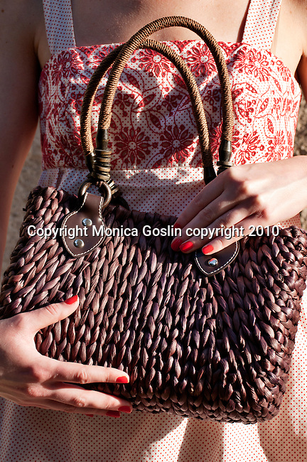 A brown straw purse from Bellagio, Italy with a red and white dress
