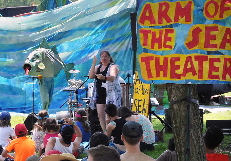 "Sign Language Interpreter, Luane Davis Haggerty, translating the words of, Arm-of-the-Sea Mask and Puppet Theater troupe, performing ""The Rejuvenary River Circus,""  near the river's edge, on the first day of the Clearwater's Great Hudson River Revival Festival 2013, held at Croton Point Park, in Croton-on-Hudson, NY, June 15, 2013. Photo by Jim Peppler. Copyright Jim Peppler 2013 all rights reserved."