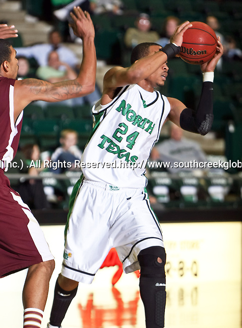 North Texas Mean Green forward Kedrick Hogans (24) prepares to pass the ball in the game between the Texas State Bobcats and the University of North Texas Mean Green at the North Texas Coliseum,the Super Pit, in Denton, Texas. UNT defeated Texas State 85 to 62