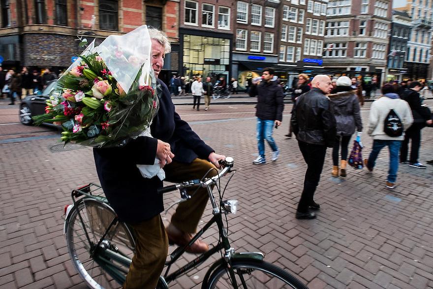 Nederland, Amsterdam, 13 dec 2014<br /> Man met enorme bos bloemen op de fiets. <br /> Foto: (c) Michiel Wijnbergh
