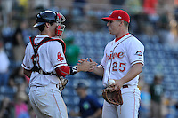 Pitcher Bobby Poyner (25) of the Greenville Drive shakes hands with catcher Austin Rei (13) after closing out a game against the Columbia Fireflies on Sunday, April 24, 2016, at Fluor Field at the West End in Greenville, South Carolina. Greenville won, 5-1. (Tom Priddy/Four Seam Images)
