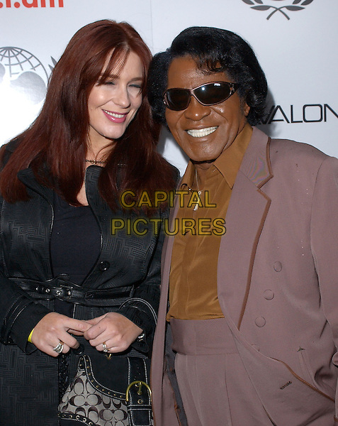 TOMMIE RAE & JAMES BROWN.Will.i.am Music Group and RBK's Tsunami Relief Benefit Concert held at Avalon in Hollywood, California .February 11th, 2005.half length sunglasse shades married husband wife purple.www.capitalpictures.com.sales@capitalpictures.com.Supplied By Capital PIctures