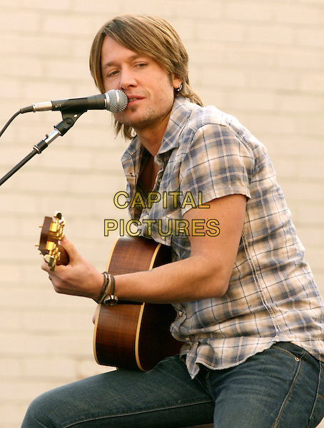 KEITH URBAN.is joined by Verizon Wireless and Samsung Mobile as he makes an in-store appearance for his fans at the Verizon Wireless store in Pasadena, California, USA, November 21st 2009                                                                   .half length music concert gig live on stage grey gray brown plaid checked check shirt microphone playing tattoo bracelets singing sitting jeans guitar .CAP/RKE/DVS.©DVS/RockinExposures/Capital Pictures
