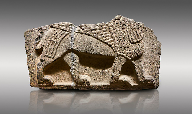 Picture & image of Hittite monumental relief sculpted orthostat stone panel from Water Gate Basalt, Karkamıs, (Kargamıs), Carchemish (Karkemish), 900-700 B.C. Anatolian Civilisations Museum, Ankara, Turkey.<br /> <br />  A portion of the body and the feet of the Sphinx. Its chest was processed as fish flakes. Parallel lines on its wings draw attention.  <br /> <br /> On a gray background.