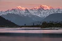 Last light and twilight with alpen glow on Southern Alps, Mount Tasman and Mount Cook with reflections in Cook River in foreground, Westland National Park, World Heritage Area, West Coast, New Zealand