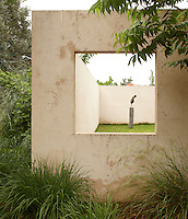 An external window allows a view into the secluded walled garden and also frames a contemporary bronze sculpture on a stone plinth