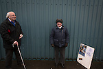 Two elderly home supporters pictured inside an entrance to the stadium before Greenock Morton take on Stranraer in a Scottish League One match at Cappielow Park, Greenock. The match was between the top two teams in Scotland's third tier, with Morton winning by two goals to nil. The attendance was 1,921, above average for Morton's games during the 2014-15 season so far.