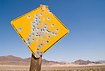 Bullet-riddled yellow diamond traffic caution sign with no message, Inyo County, Calif.