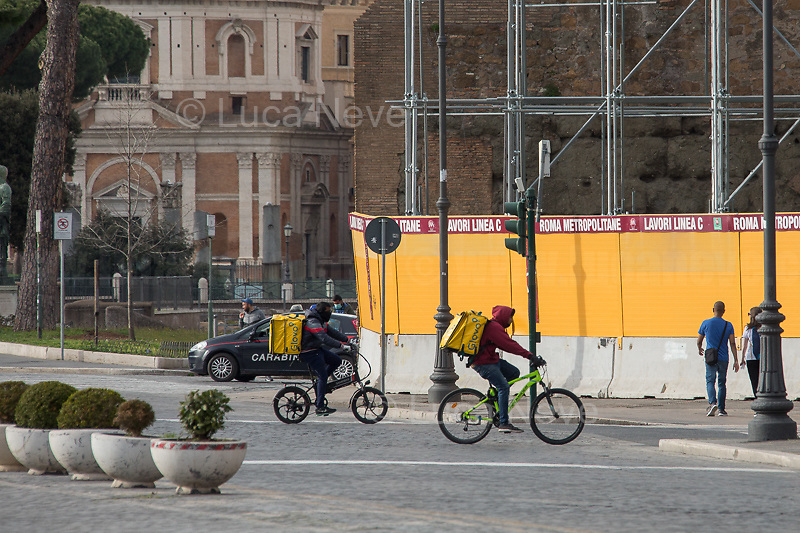 """Food Runners and Delivery: allowed.<br /> <br /> Via dei Fori Imperiali.<br /> <br /> Rome, 12/03/2020. Documenting Rome under the Italian Government lockdown for the Outbreak of the Coronavirus (SARS-CoV-2 - COVID-19) in Italy. On the evening of the 11 March 2020, the Italian Prime Minister, Giuseppe Conte, signed the March 11th Decree Law """"Step 4 Consolidation of 1 single Protection Zone for the entire national territory"""" (1.). The further urgent measures were taken """"in order to counter and contain the spread of the COVID-19 virus"""" on the same day when the WHO (World Health Organization, OMS in Italian) declared the coronavirus COVID-19 as a pandemic (2.).<br /> ISTAT (Italian Institute of Statistics) estimates that in Italy there are 50,724 homeless people. In Rome, around 20,000 people in fragile condition have asked for support. Moreover, there are 40,000 people who live in a state of housing emergency in Rome's municipality.<br /> March 11th Decree Law (1.): «[…] Retail commercial activities are suspended, with the exception of the food and basic necessities activities […] Newsagents, tobacconists, pharmacies and parapharmacies remain open. In any case, the interpersonal safety distance of one meter must be guaranteed. The activities of catering services (including bars, pubs, restaurants, ice cream shops, patisseries) are suspended […] Banking, financial and insurance services as well as the agricultural, livestock and agri-food processing sector, including the supply chains that supply goods and services, are guaranteed, […] The President of the Region can arrange the programming of the service provided by local public transport companies […]».<br /> Updates: on the 12.03.20 (6:00PM) in Italy there 14.955 positive cases; 1,439 patients have recovered; 1,266 died.<br /> <br /> Footnotes & Links:<br /> Info about COVID-19 in Italy: http://bit.do/fzRVu (ITA) - http://bit.do/fzRV5 (ENG)<br /> 1. March 11th Decree Law http://bit.do/fzREX (ITA) - http://bit.do/fzR"""