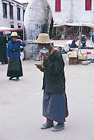 An old man walks through the streets of the Barghor Market in Lhasa on his way to the Jokhang Temple. He has not only prayer beads but also a prayer wheel that he turns continuously.