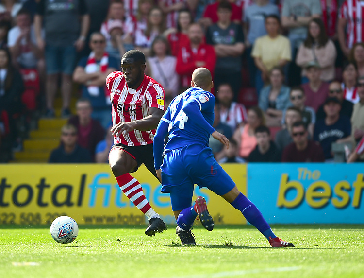 Lincoln City's John Akinde vies for possession with Tranmere Rovers' Jake Caprice<br /> <br /> Photographer Andrew Vaughan/CameraSport<br /> <br /> The EFL Sky Bet League Two - Lincoln City v Tranmere Rovers - Monday 22nd April 2019 - Sincil Bank - Lincoln<br /> <br /> World Copyright © 2019 CameraSport. All rights reserved. 43 Linden Ave. Countesthorpe. Leicester. England. LE8 5PG - Tel: +44 (0) 116 277 4147 - admin@camerasport.com - www.camerasport.com