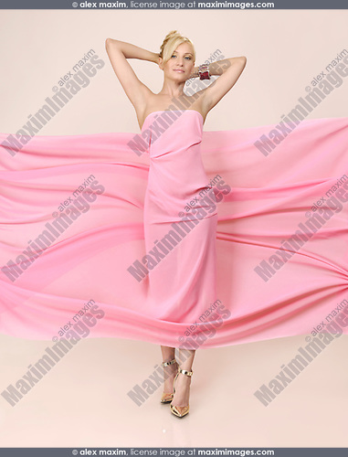 Beautiful young woman in wrapped in pink flowing fabric